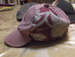Basic ball cap.  First attempt.  Tommy Hilfiger shirt and curtain material with custom button.  Ribbon hat band and yogurt container brim stiffener.